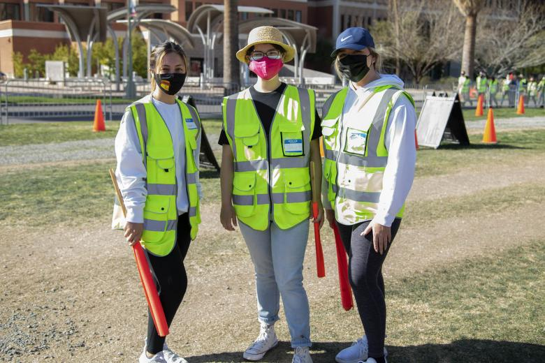UArizona Health Sciences students Rebecca Lynn Amador, Ashley Casarez and Dariana Fimbres volunteer as traffic directors at the UArizona Point of Distribution in Pima County.