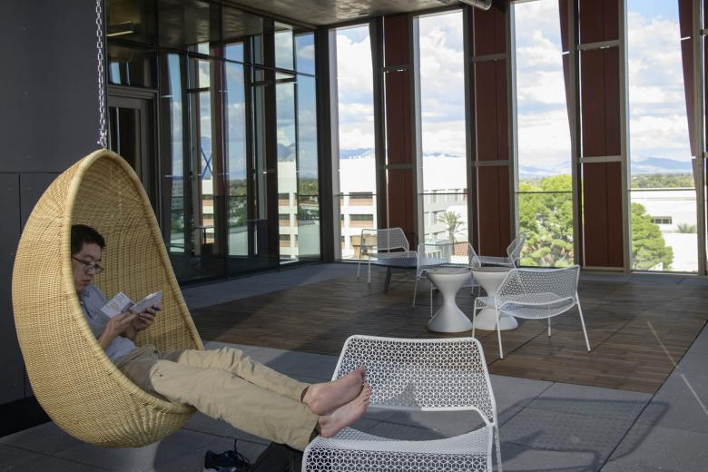 The Health Sciences Innovation Building is filled with cool and creative spaces to study, or just hang around – like this student on the sixth-floor open-air balcony where there are two hanging wicker chairs.
