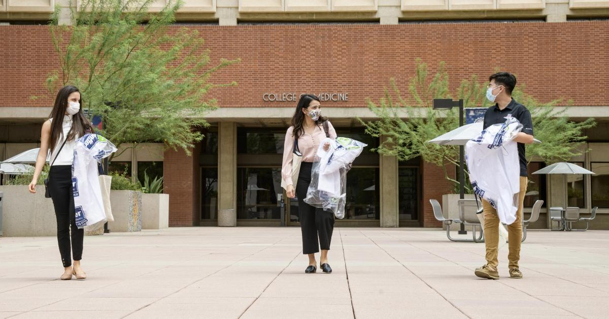 Students in the College of Medicine – Tucson Class of 2024 wear masks and keep a safe distance from one another as they pick up their white coats, the traditional activity marking the beginning of their four-year medical school experience.