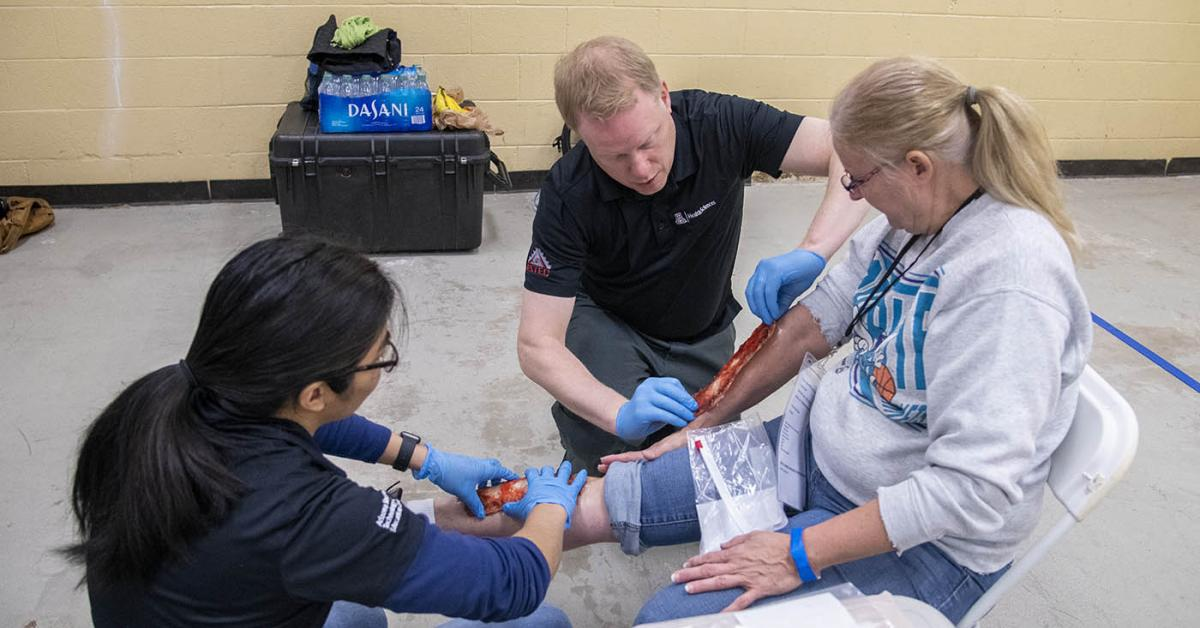 Merryl Lopido, simulation operations specialist for ASTEC, and David Biffar, ASTEC's assistant director of operations, use special-effects makeup to simulate traumatic injuries on volunteer Helen Ward's leg. Many volunteers received simulated wounds with fake blood or embedded debris.