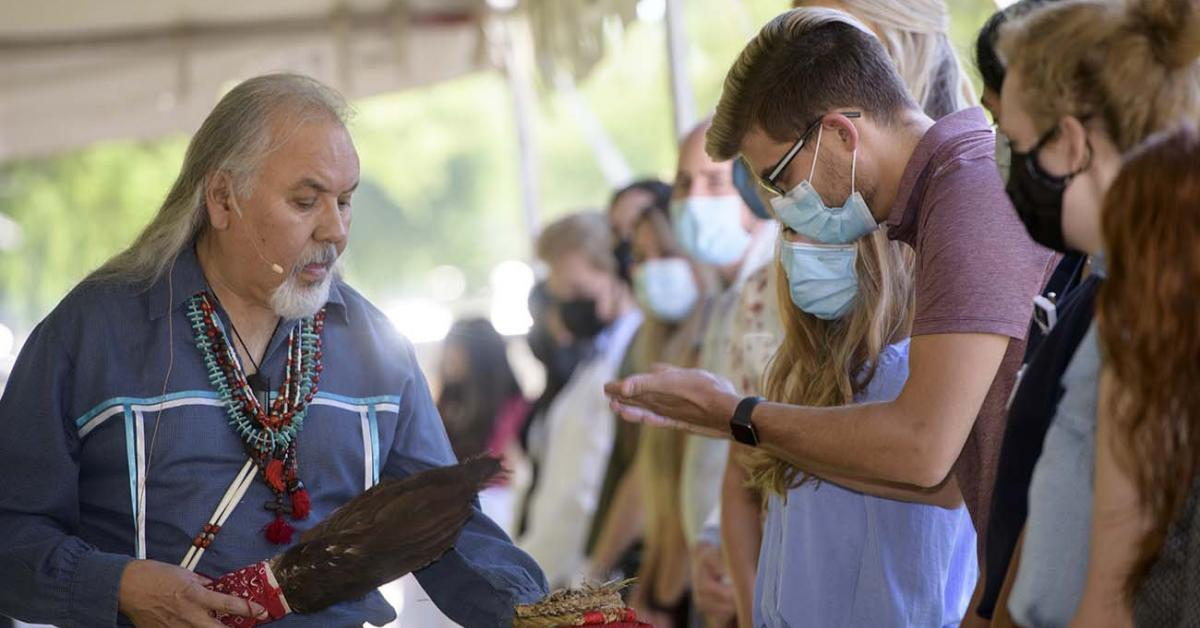 During the smudging ceremony, Dr. Carlos Gonzales holds the shell containing the burning herbs for a student to pull the smoke over himself as part of the blessing.