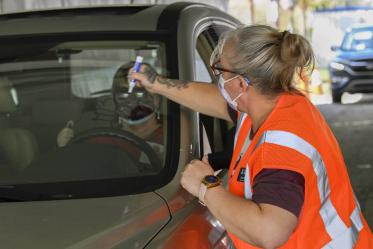 After receiving a vaccine, each driver must wait 15 minutes in their car to ensure no immediate side effects. At the University of Arizona vaccine distribution site, a volunteer writes the vaccination time on a driver's window.