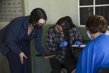 Dr. Nicole Henry, assistant professor at the College of Pharmacy in Phoenix, holds a tablet with information assisting pharmacy student Lisa Wan as she fills out a vaccination card for a vaccine recipient.