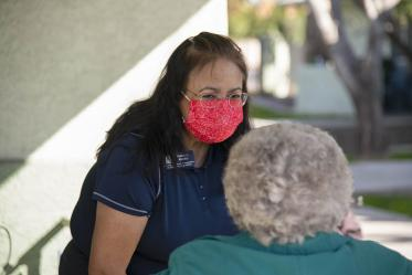 Nancy Alvarez, College of Pharmacy associate dean of academic and professional affairs for Phoenix, speaks with an elderly vaccine recipient from El Mirage Senior Village public housing complex. Patients stay under observation for 15 minutes after receiving the vaccine to make sure there are no adverse reactions.