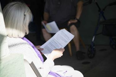 A resident from El Mirage Senior Village reads information about the COVID-19 vaccine as she waits to receive the first dose.