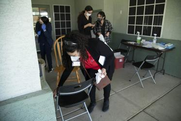 Maria Jaime, health educator from the College of Public Health in Phoenix, sanitizes a chair before the next patient sits down to receive the COVID-19 vaccine.