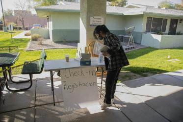 Second-year College of Pharmacy student Lisa Wan helps set up the check-in table in the courtyard of El Mirage Senior Village in El Mirage, Arizona.