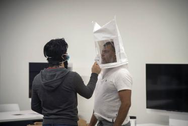 First-year College of Medicine – Tucson student Ahmed Al-Shamari sprays bitters into second-year medical student Waheed Asif's hooded mask so he can identify their taste during subsequent tests in full protective equipment.