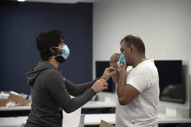 First-year College of Medicine – Tucson student Ahmed Al-Shamari checks second-year student Waheed Asif's N95 mask to ensure it has a good seal.