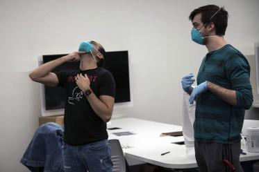 Second-year College of Medicine – Tucson student Alexandre Cavalcante adjusts his N95 mask as student-volunteer Billy Evans watches.