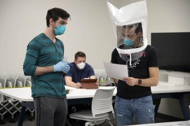 First-year College of Medicine – Tucson student Billy Evans observes second-year student Alexandre Cavalcante reading a passage as part of the fitting exercises.