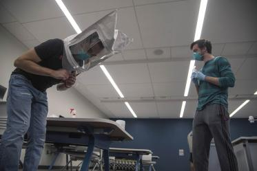 Under the watchful eye of student-volunteer Billy Evans, second-year College of Medicine – Tucson student Alexandre Cavalcante bends over while wearing a hood and his N95 mask. This is one of seven exercises the students must do during the mask-fit test.
