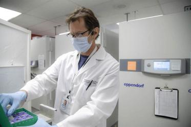 Michael Badowski, PhD, pulls out a vial containing the Pfizer vaccine that will be used at the University POD.