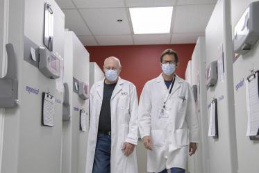 Drs. David Harris and Michael Badowski walk through the freezer farm to collect more vaccines for distribution.