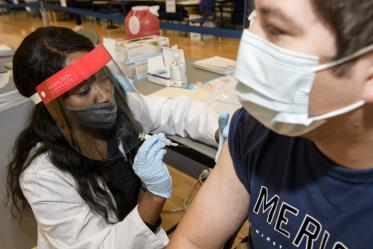 "College of Pharmacy student Judy Mburu administers a flu vaccination to a student, hoping to create a comfortable environment to help patients feel at ease. ""When you, as the immunizer, get comfortable, the patient will also get comfortable,"" Mburu says ""They're not going to feel afraid or worried."""
