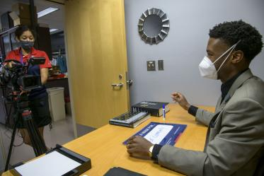 """During video production for the """"I Wear a Mask"""" campaign, Viola Watson, videographer for the UArizona Health Sciences Office of Communications, interviews Ike Chinyere,MD/PHD student, at the College of Medicine – Tucson, as he discusses the importance of wearing a mask."""