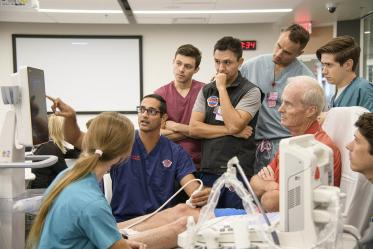 Emergency medicine residents gather around a standardized patient to learn how to administer ultrasound for different injuries.