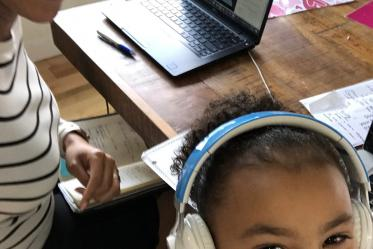 Allison Otu, executive director of corporate and community relations, poses for a photo with her daughter while working from home.
