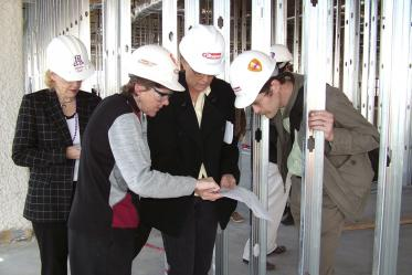 Faculty and staff inspect blueprints on their tour of Roy P. Drachman Hall, 2005. Pictured from left: Chris Tisch; Denise Roe, DrPH; Linda Temellie; Jim Ranger-Moore.