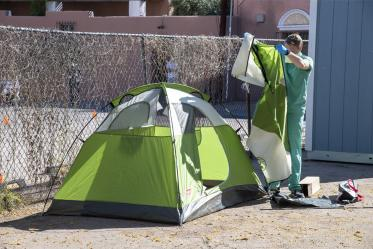 "College of Medicine – Tucson student Chris Vance helps set up a tent at the Z Mansion in downtown Tucson in April. Homeless individuals with potential or suspected coronavirus infection are isolated outdoors in tents on the property. These makeshift ""wards"" are staffed by UArizona medical students, who distribute food three times a day and monitor patients for worsening conditions."