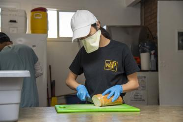 Koustubh Kandapalli slices bread to prepare meals to distribute to Tucson's homeless population. The medical student is volunteering to serve the vulnerable population during the COVID-19 pandemic.