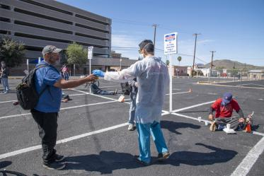 Christian Bergman hands out beverages at Tucson's Z Mansion soup kitchen. He and other medical students are volunteering to provide health care services to the vulnerable homeless population.
