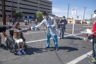 Christian Bergman and Shrey Goel offer a drink to a person in the parking lot of the Z Mansion, a soup kitchen for Tucson's homeless population.
