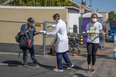 Medical students in the College of Medicine – Tucson serve food and beverages while offering health care to Tucson's homeless population as part of the College's Commitment to Underserved People program.