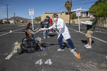 A student in the College of Medicine – Tucson offers food and drink to a woman at Z Mansion, a soup kitchen for homeless people several times a week. They try to keep a safe distance to prevent potential spread of COVID-19 virus.