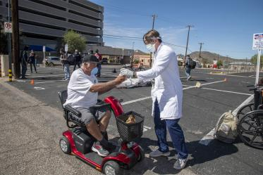 Students in the College of Medicine – Tucson distributed food, water and medical care to the homeless population in downtown Tucson during the pandemic. Pictured here in April near the Z Mansion, a food distribution site for the homeless population several times a week.