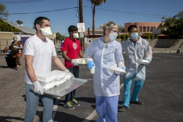 Medical students Jaime Contreras, Shrey Goel and Christian Bergman prepare to distribute food and drinks to homeless residents in Tucson who visit the Z Mansion soup kitchen. The students are also offering a medical clinic to help the vulnerable population during the global pandemic of COVID-19.