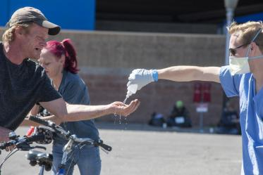 A student in the College of Medicine – Tucson helps a man sanitize his hands. Students are helping homeless people during the pandemic, because the medically-vulnerable population is expected to be hit hard by the COVID-19 virus.