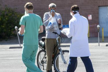 Chris Vance (right) and another College of Medicine – Tucson student offer food, drinks and medical services to the homeless population served at Z Mansion several times a week.