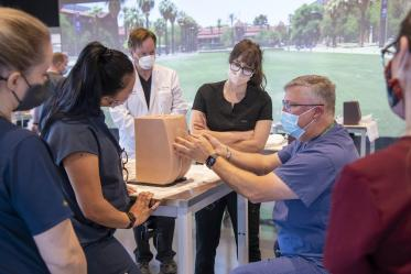 Chris Herring, DNP, CRNA, demonstrates lumbar puncture techniques to Adult-Gerontology Acute Care Nurse Practitioner (AGACNP) students at ASTEC. The ACAGNP clinicians use this technique to collect samples of cerebral spinal fluid  to assist in the diagnosis of diseases of   the neurological system.