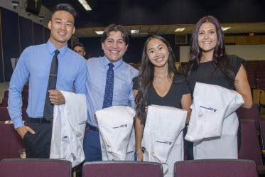 Medical students Brandon Zhang, Luis Novelo Hernandez, Nicole Kummet, and Emily Dereskiewicz pose for a photo before the start of the Class of 2025 white coat ceremony at Centennial Hall.