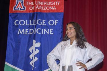Gisselle Pegaitaz poses in front of the UArizona College of Medicine – Tucson banner after receiving her white coat.