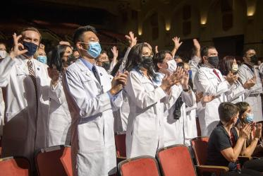 Class of 2025 medical students applaud at the end of their white coat ceremony.