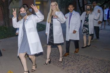 Issa Jimenez Espinoza gives two V signs as she and her classmates Megan Taylor, Brenn Belone, Lacey Hart and Curtis Mcguire leave Centennial Hall after participating in the Class of 2025 white coat ceremony.