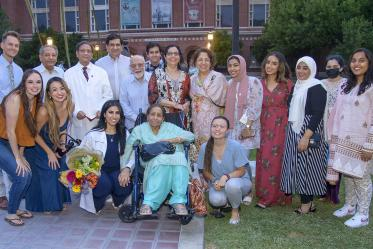 UArizona College of Medicine – Tucson's Duri Sabina Saeed, kneeling with flowers, poses for a photo with her family and friends after the Class of 2025 white coat ceremony at Centennial Hall.