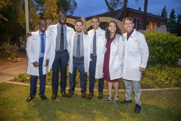 UArizona College of Medicine – Tucson classmates, from left, Toluwalase Talabi, Ayomide Odeneye, Ben Litmanovich, Sascha Delzepich, Aseel Ibrahim and Max Coffeen pose for a photo outside of Centennial Hall after receiving their white coats.