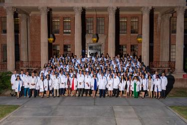 UArizona College of Medicine – Tucson Class of 2025 faculty and staff gather for a group photo in front of Cochise Hall after the white coat ceremony.
