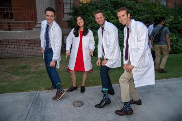 """Newly """"white-coated"""" medical students, from left, Riley Hellinger, Coco Victoria Gomez Tirambulo, Mathew Flower and Zak Webber show off their """"doctor"""" socks."""