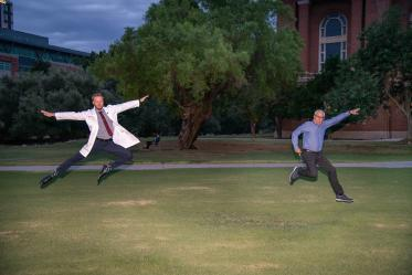 Medical student Matthew Flowers and his father Clifford Flowers jump for joy after Matthew received his white coat at the ceremony.