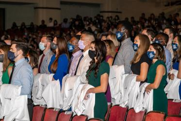 Medical students recite the mission statement during the Class of 2025 white coat ceremony at Centennial Hall.