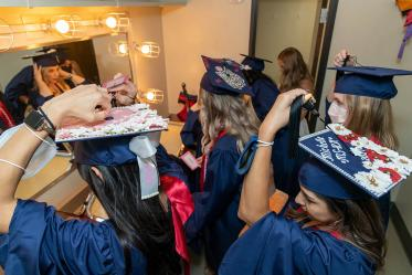 Graduates arrange their highly decorated graduation caps before the start of the college's August commencement ceremony.
