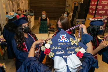 College of Nursing graduates prepare backstage at Centennial Hall before their commencement ceremony.