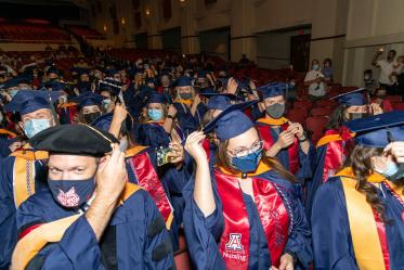 Graduates turn their tassels at the conclusion of the  August commencement at Centennial Hall.