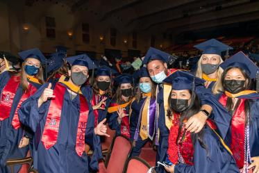 Graduates pose after commencement at Centennial Hall.
