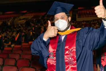 A graduate gives the thumbs up as he exits after the August commencement at Centennial Hall.
