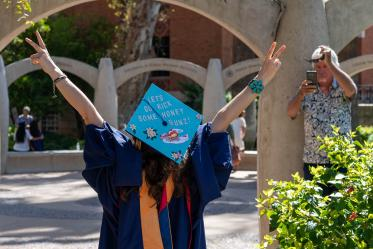 Hailey Sexton raises her arms victoriously after the College of Nursing graduation ceremony.